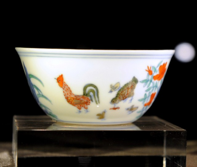 A woman looks at the Meiyintang Chenghua 'Chicken Cup' on display during Sotheby's spring sales in Hong Kong on April 5, 2014. The 'Chicken Cup' is expected to fetch 25 to 38 million USD when it goes up for sale on April 8. AFP PHOTO / DALE DE LA REY