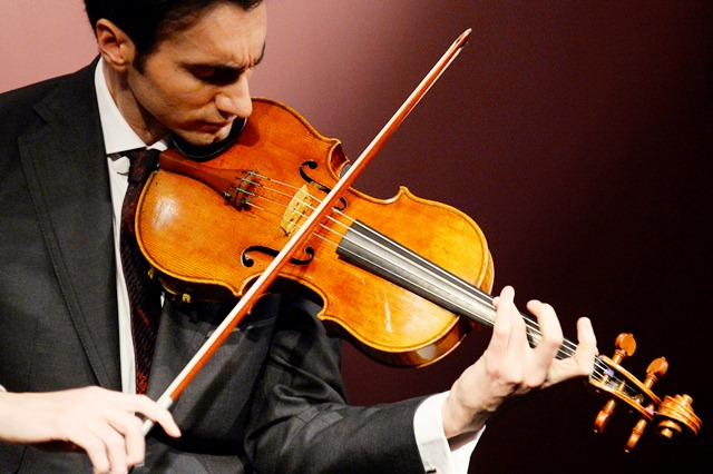 """US violist David Aaron Carpenter plays the """"Macdonald"""" Stradivarius viola created in 1719 by Antonio Stradivari (1641-1737), at Sotheby's auction house in Paris on April 15, 2014. Sotheby's announced the sale of the viola for this spring 2014 in New York, estimated to sell in excess of 45 million US dollars.  AFP PHOTO BERTRAND GUAY"""