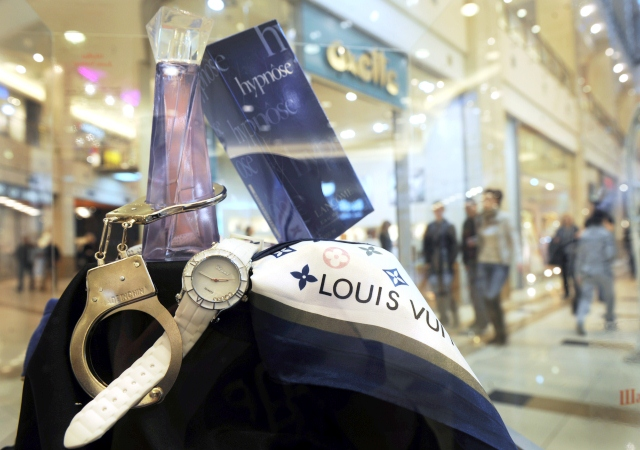 A counterfeit Louis Vuitton scarf, Lancome perfume and Chopard wristwatch are displayed at an exhibition of counterfeit goods of famous trademarks in the Bulgarian capital Sofia on March 16, 2011. Bulgaria's customs agency seized in 2010 a total of 2.5 million goods with breached trademark rights.           AFP PHOTO / NIKOLAY DOYCHINOV