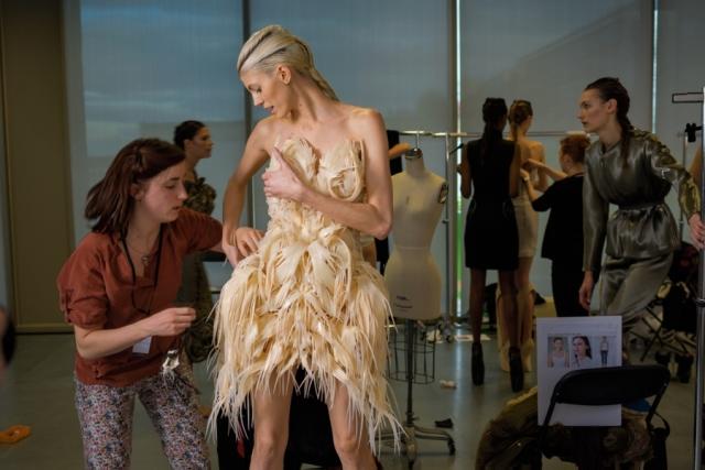 Модель Девон Виндзор готовится к выходу на модном показе Ready to Wear в Париже. Ее платье – плод сотрудничества кутюрье и архитектора, распечатанный на 3D-принтере. Ирис ван Херпен (дизайнер); Джулия Корнер (архитектор). Произведено при участии компании Materialise.