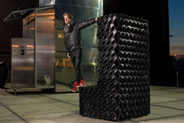 Архитектор Ганс Вермулен позирует на распечатанном 3D-принтером угловом камне здания на берегу амстердамского канала.